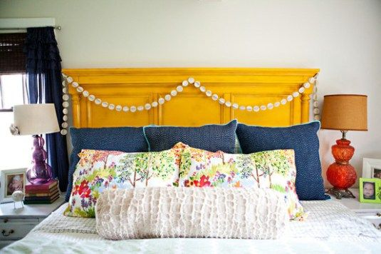 Yellow headboard, denim pillows, fun banner drape... nailed it...