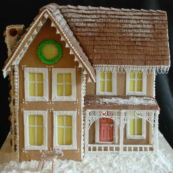 This was made using a classic Victorian gingerbread blueprint. Jelly candy rocks make up the chimney, and chocolate fondant with corn starch snow make up the roof. Yellow edible paper creates the glowing windows.  Created by Kenna N. of Louisville, KY.