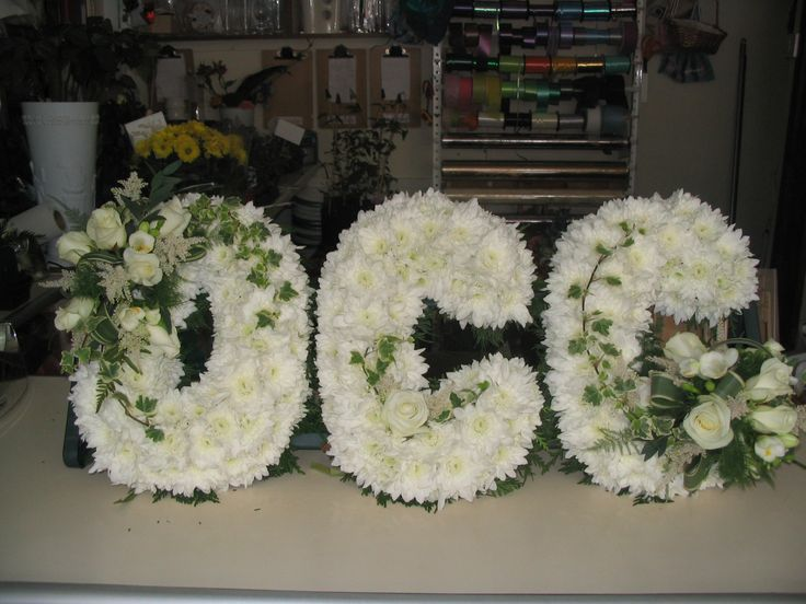 Based letter in white with a couple of sprays of white flowers and foliage.