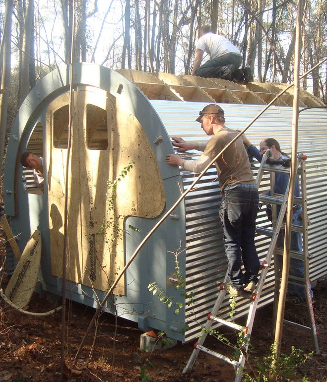 Volunteers for Mad Housers Inc. build an enclosure out of