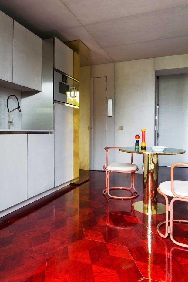 Esta criação usa um pano de fundo alvo para receber arroubos de criatividade. Só uma base branca seria capaz de acomodar, ao mesmo tempo, um piso vermelho de marchetaria e detalhes arquitetônicos dourados. Ousado e muito chique!