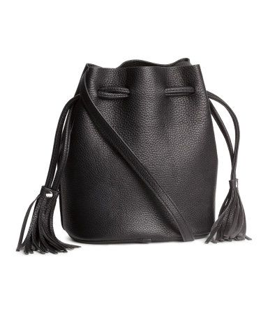 Small black bucket bag in grained imitation leather with a drawstring at the top, tassel details, & an adjustable shoulder strap. | H&M Accessories