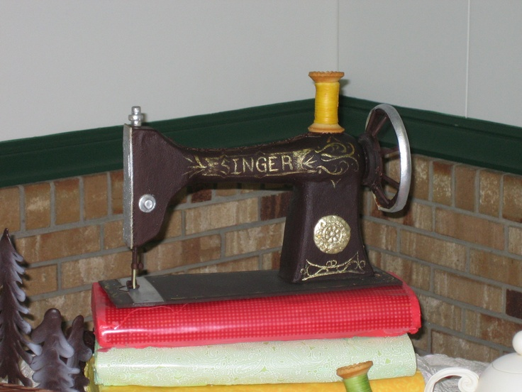 Chocolate life sized sewing machine sitting on bolts of fabric that are actually cake.