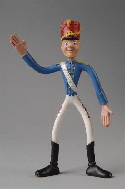 "Rubberen Kwatta-soldaatje, dun en slungelig figuurtje met buigbare ledematen, blauw uniformjasje, witte broek en rode sjako, op witte sjerp ""KWATTA"""