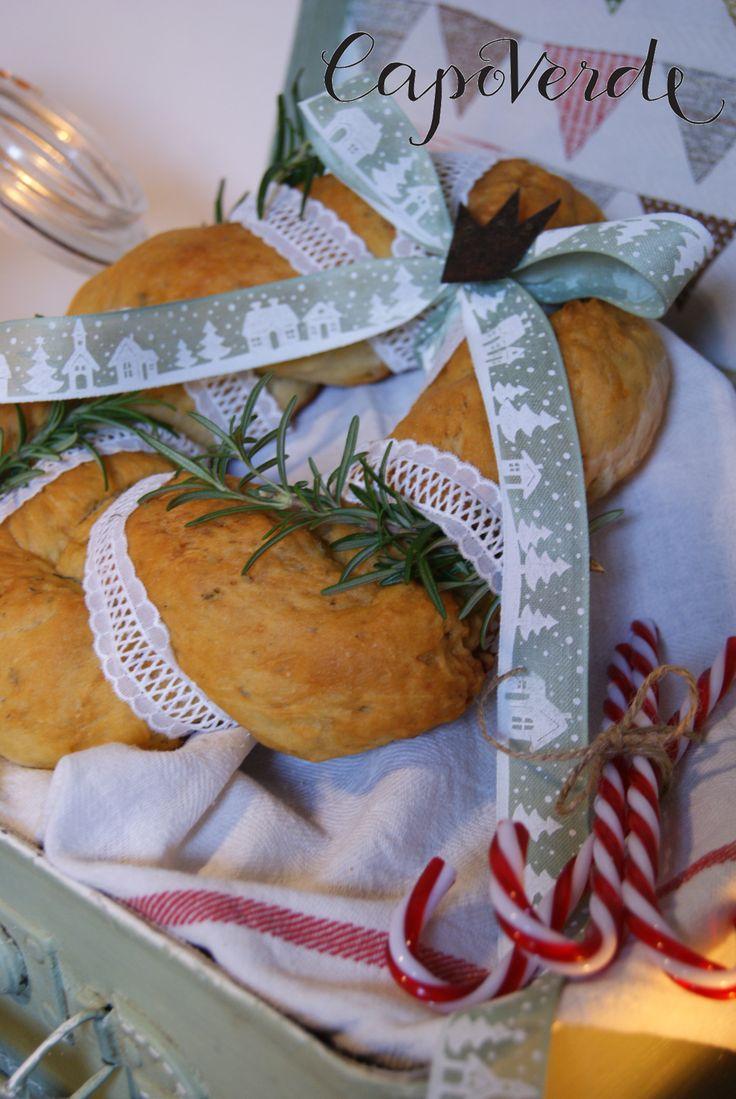 Una deliziosa ghirlanda di pane al rosmarino impreziosita da un semplice nastro decorato, del pizzo sangallo e da una coroncina arruginita. Una vecchia valigia, i candy canes e la luce fioca di una candela.