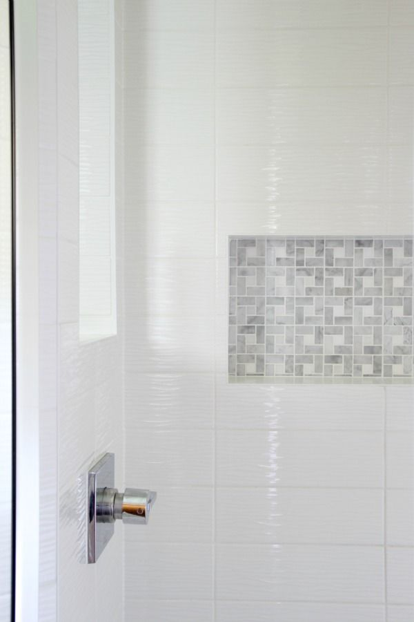 A frameless glass door and sidelights allow light to flow freely into the once dark shower. A wall niche for toiletries and an overhead rain shower head were space-saving measures that also feel luxurious.