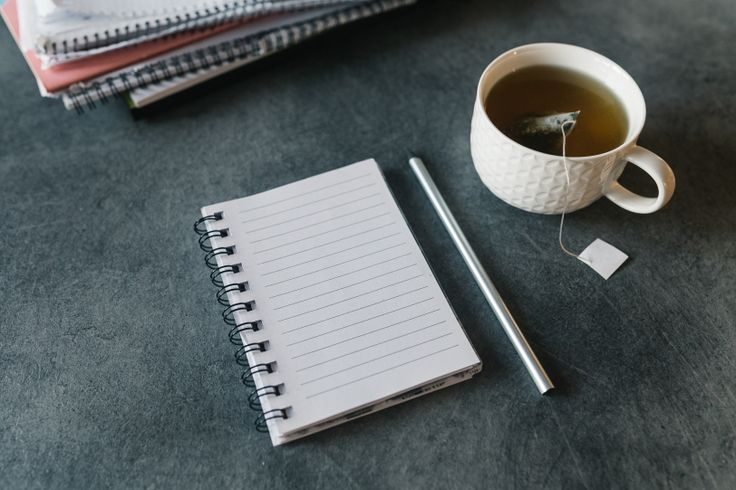 FREE STOCK PHOTO: Blank empty notepad, pencil and cup of tea on grey desk