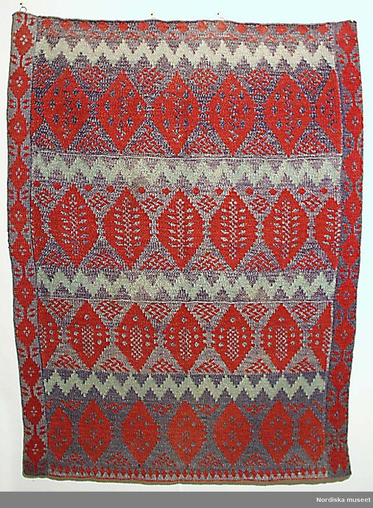 Täcke, stickat i mönster av rött och gult ullgarn. Tillverkat av Märta Stina Persson (Märta Stina Abrahamsdotter), Ångermanland. NM 144603. @ DigitaltMuseum.se