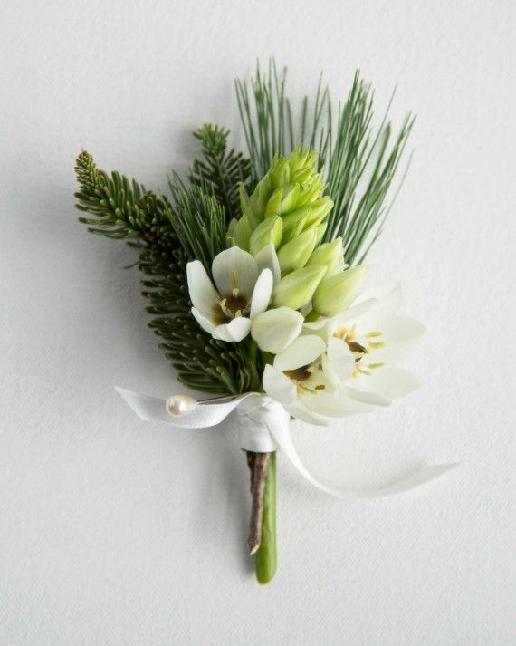 Classic meets exotic with this lush boutonniere expertly pairing white pine needles, balsam fir and a South African cape chincherinchee blossom. Using unexpected blooms helps add a distinct element, while the evergreen elements keeps it seasonal.