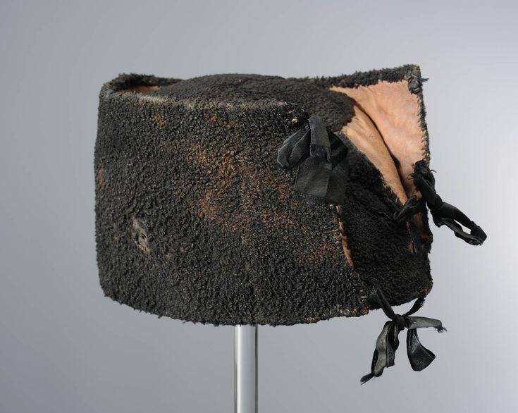 karpoets van bont, Urk, voor 1944. Voor WWII droeg wie het betalen kon karpoets van bont van ongeboren lam. In de oorlog was dit materiaal niet meer te krijgen en ging men de karpoets of karpoes van een ruw soort wollen laken maken. Tot dan toe noemde men dit 'armeluis karpoesen'. De karpoets werd 's winters gedragen, 's zomers droegen de Urker mannen een hoed. De strikjes werden aanvankelijk achter en later steeds meer aan de voorkant gedragen. Het binnenwerk van de karpoes is van leer…
