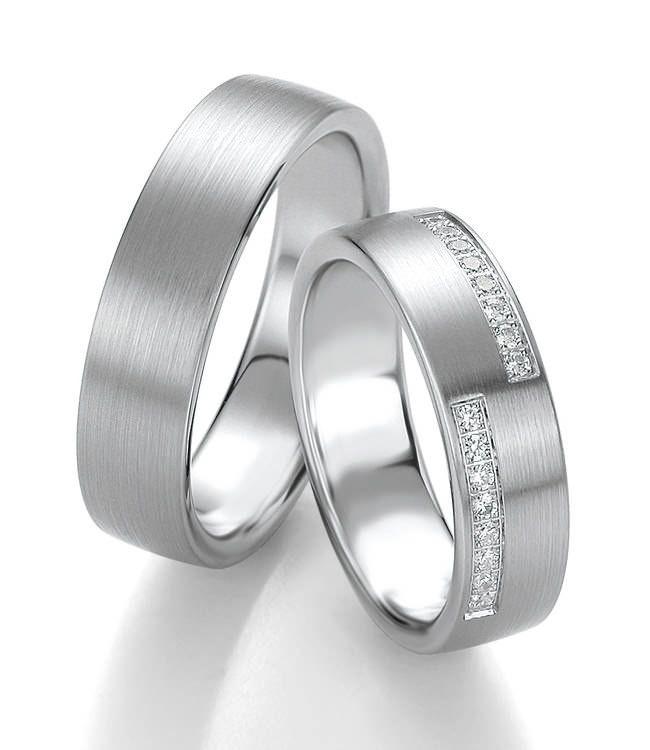 Elegante Eheringe in Platin. Der Damenring ist links und recht mit funkelnden Diamanten geschmückt.