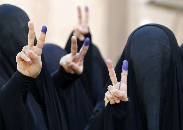 OBJETIVO 5: IGUALDADE DE GÊNERO Mulheres iraquianas completamente cobertas por véus fazem o gesto da vitória com seus dedos manchados por tinta depois de votar nas primeiras eleições iraquianas desde a invasão dos EUA. Elas foram fotografadas no distrito comercial de Karrada, em Bagdá 5 - Sabah Arar/AFP/Getty Images