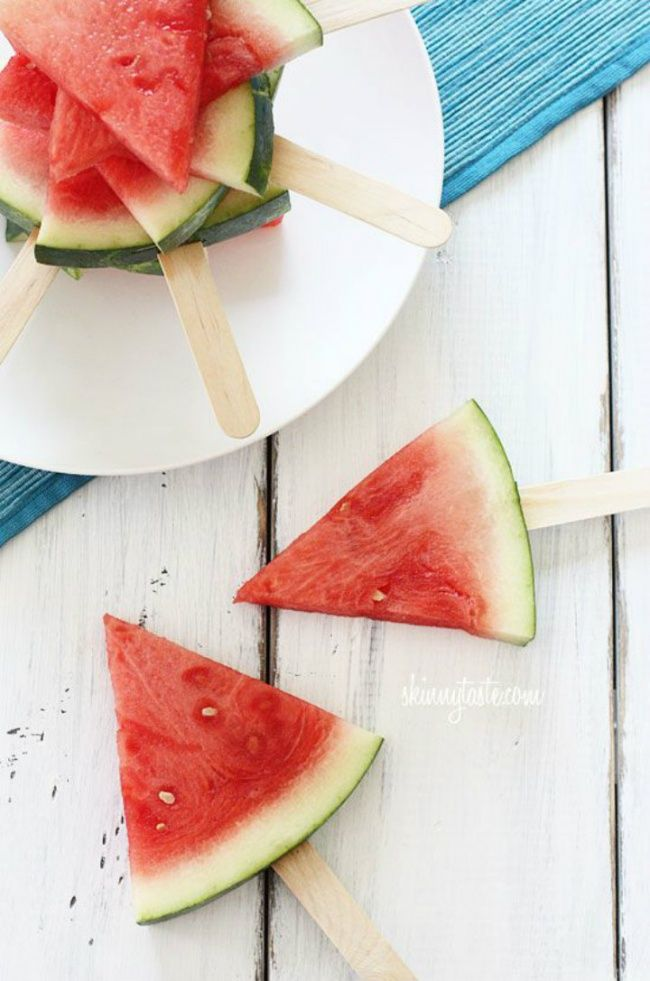 To serve a watermelon in the most convenient way, cut it into triangles and put each piece on a popsicle stick.