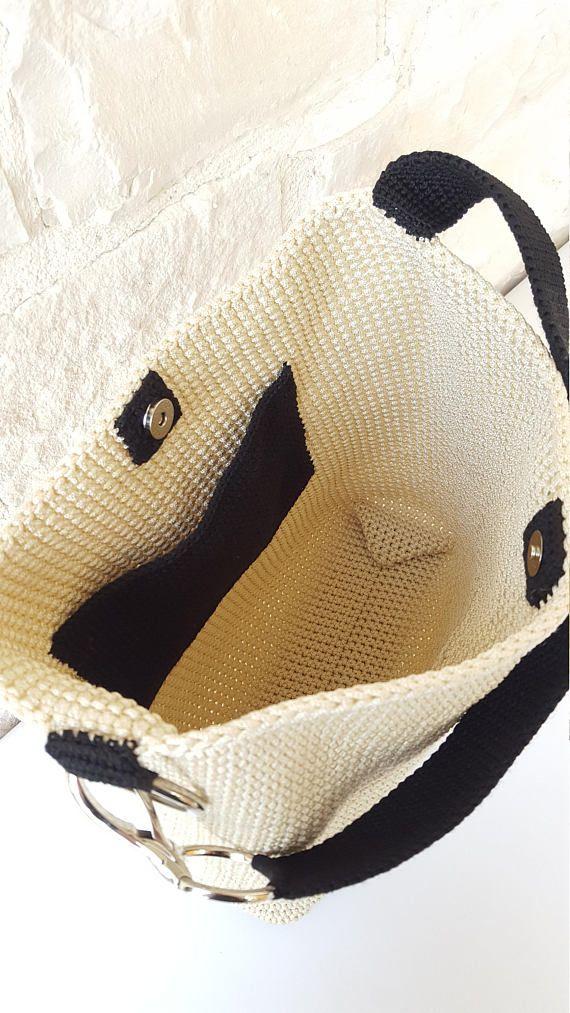 Hobo bag in cordino panna e nero. Abbinamento perfetto questo per creare una borsa stilosa, pratica e perfettamente abbinabile a ogni outfit da giorno. La borsa è dotata di una chiusura magnetica. Tasca interna applicata in cordino nero Manico a spalla in cordino nero con grande moschettone finitura nickel Dimensioni: A 32 cm L 32 cm P 8 cm Altezza manico 35 cm