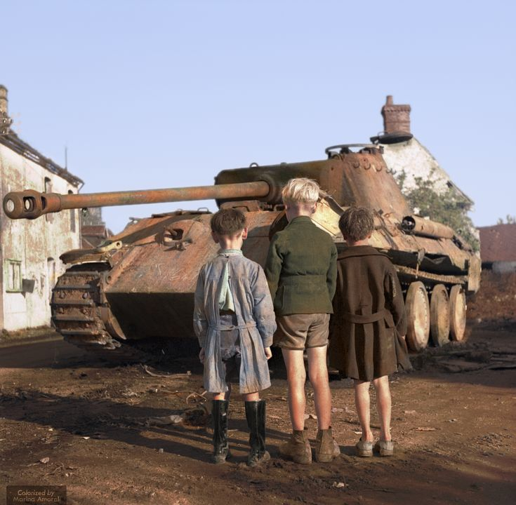 Colorized by me: Three French boys looking at a knocked-out German Panther tank in the Falaise pocket Normandy 25th of August 1944 [1810x1772]