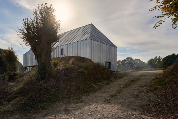 Renovated by Antonin Ziegler Architecte, inNotre-Dame-de-Bliquetuit, France, the barn features a shell of zinc that covers the roof and walls to conserve the monolithic, agricultural architecture.