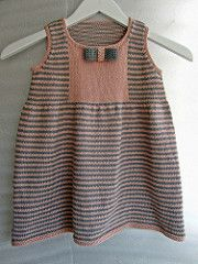 This little girl's dress is all about contemporary, candy-striped appeal, but in a shape that harks back to the traditional pinafore. Knit in stockinette stitch with garter stitch edgings, the dress features a plain-panel yoke, playful attached bow and gentle gathers that give a slight flare to the skirt. In mint green and ecru Eco Baby yarn, an organic, Fair Trade cotton.