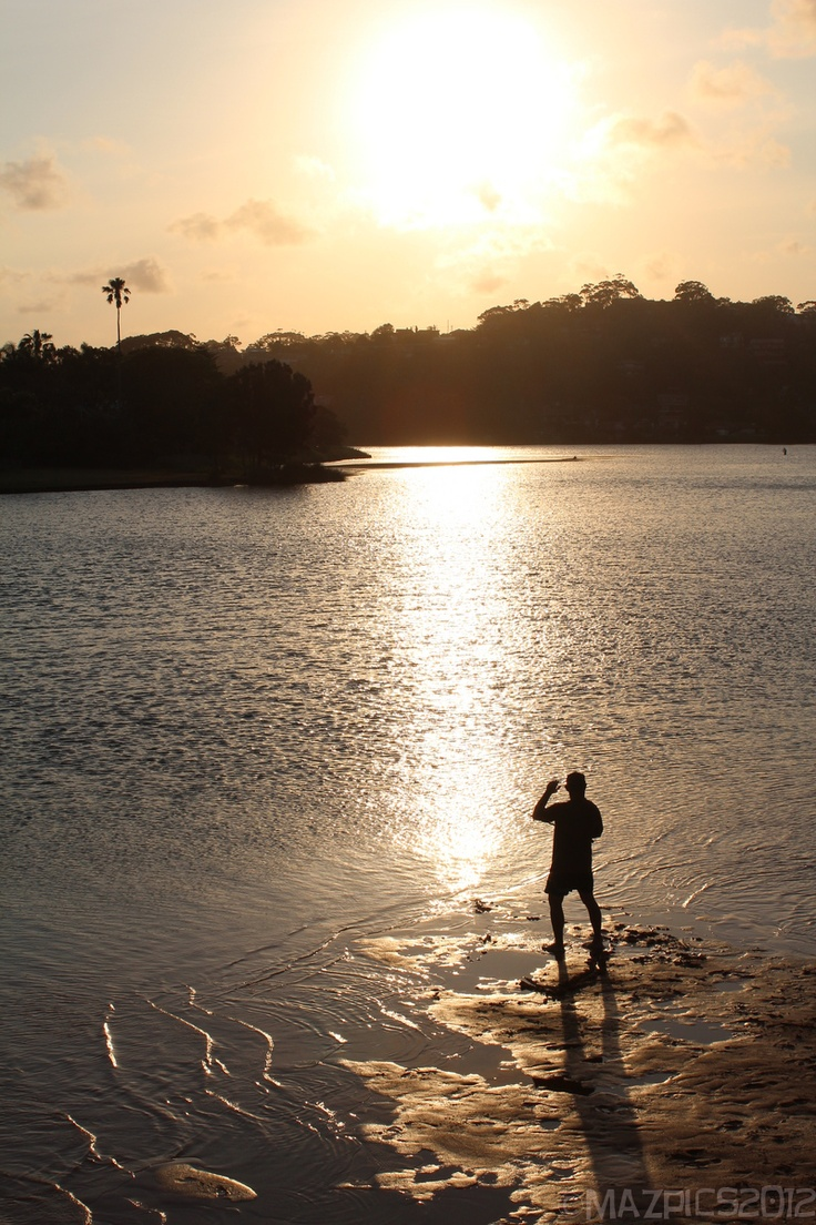 A man fishing where the lake meets the sea - North Narrabeen, Sydney, Australia