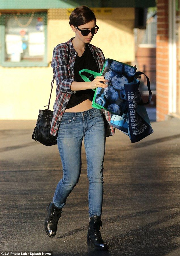 Flawless! The daughter of musician Phil Collinsshowed off her fabulous figure in a black cropped top which flaunted her toned tummy