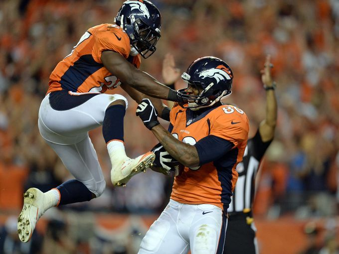 Denver Broncos tight end Julius Thomas (80) reacts with running back Knowshon Moreno (27) after scoring his first touchdown reception in the second quarter against the Baltimore Ravens at Sports Authority Field at Mile High.