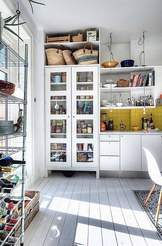 Even if you're not a fan of the open shelving look, there are a few great ideas in this Scandinavian kitchen: a nook above the semi-see-through pantry closet for shopping baskets, suspended lights over the countertop, a yellow tile (!) backsplash that wraps around the wall.