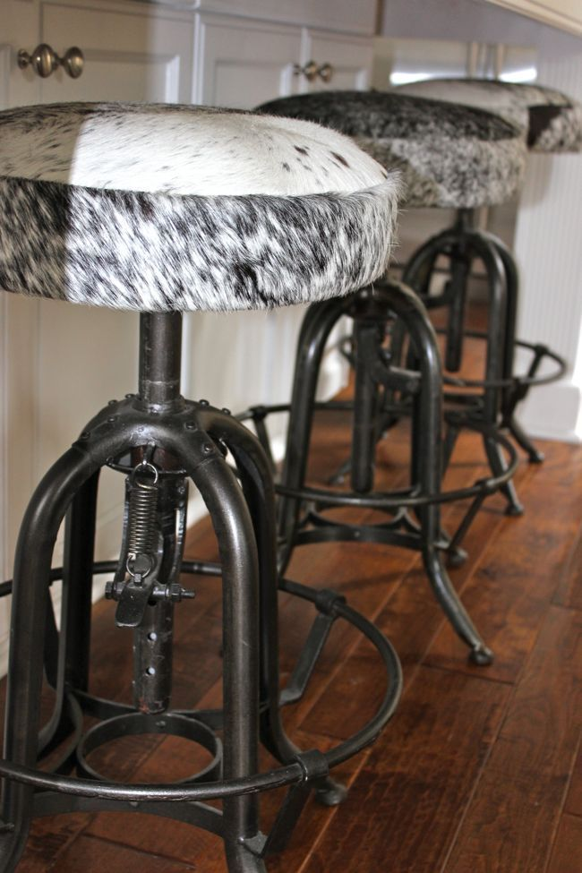 Cowhide bar stools with an industrial base mixes two styles perfectly