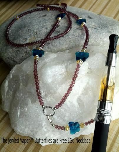 """The Jeweled Vaper """"Butterflies Are Free"""" Necklace. DESCRIPTION - Swarovski Crystal Blue Butterflies w/250 x 6mm Mauve Crystals and 14 x 7mm Champagne Crystals. Sliver clasp to detach from EGo (or 510) Stainless Steel Ring Holder so it can be a Charm or the latest style Y Necklace. Strung on 49 strand wire stainless steel wire. Professionally Designed/Hand Crafted by an Experienced & Professional Jeweler. Retail 240.00"""