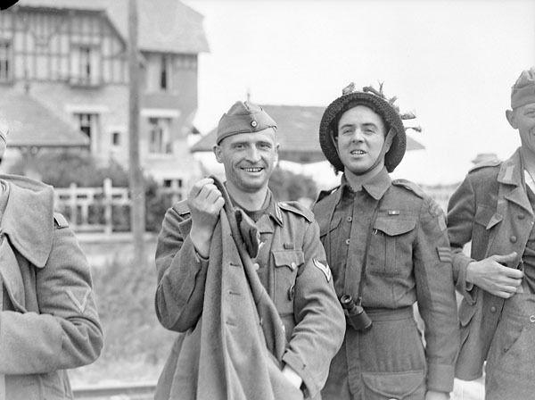 Sergeant R. Gagnon of Le Régiment de la Chaudière with a German prisoner on Nan White Beach, Bernières-sur-Mer, France, 6 June 1944. Photographer: Frank L. Dubervill