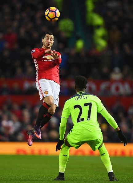 Henrikh Mkhitaryan of Manchester United jumps for the ball as Divock Origi of Liverpool looks on during the Premier League match between Manchester...
