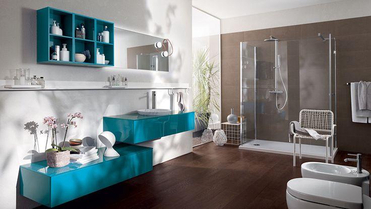 FONT  Nuova tonalità (il colore Turchese) per le basi sospese in vetro e i vani a giorno laccati, entrambi lucidi. Sul piano in vetro lucido (profondità 52 cm), il lavabo Ibo in marmo bianco di Carrara.
