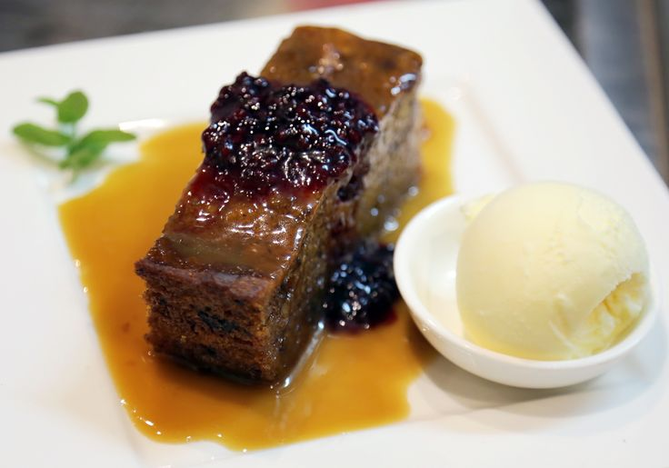 Pear Tree Cafe's Sticky Date Pudding. Served with Italo's Mouth Watering Caramel Sauce. A side of Ice Cream & Raspberry Coulis on top.