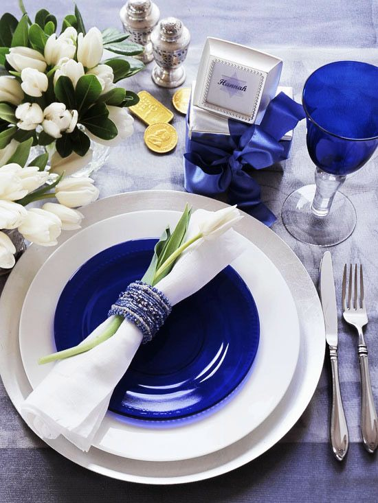 Blooming Napkin---Flowers are lovely additions to any party table setting. Here a perfect white tulip graces each napkin. Create your own floral holiday table by placing a red rose, sprig of evergreen, or even a silk flower under the napkin ring.