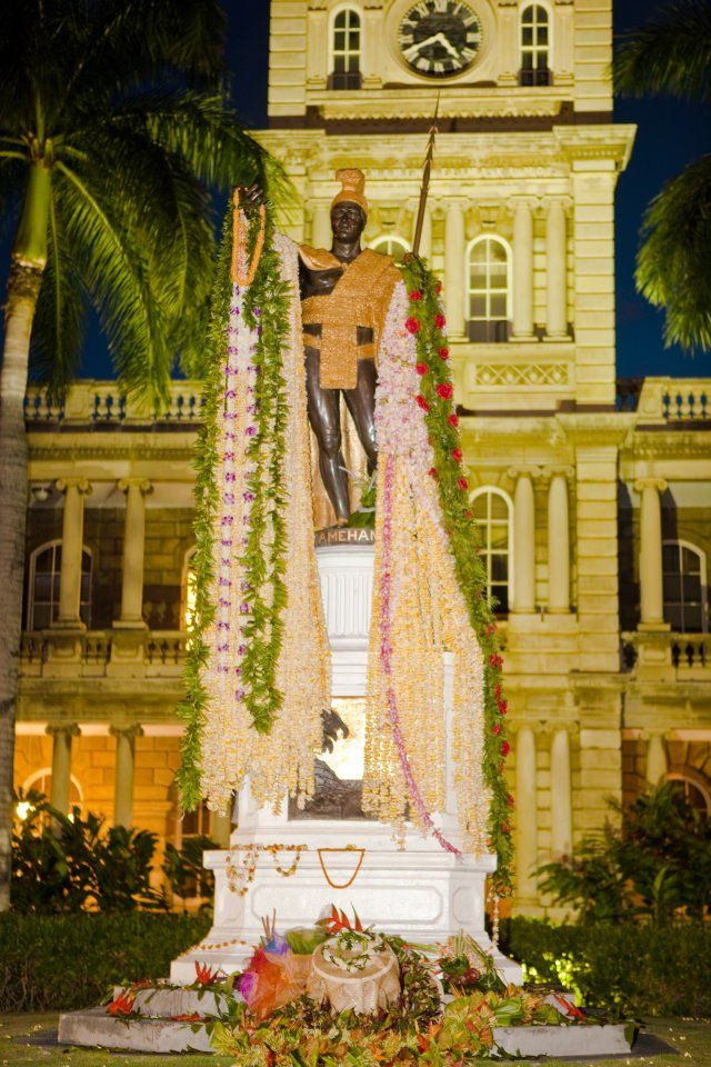 """The State of Hawaii celebrates the June 11, 1758 birth of King Kamehameha the Great; who united the Hawaiian Islands into one kingdom in 1810. This gilt statue of him sits in front of the Hawaii State Supreme Court building (some will recognize this as Hawaii Five-0's """"headquarters"""" in the TV series), directly across the street from 'Iolani Palace. Each year his statue is draped with plumeria and ti leaf leis, and gifts of food, fruit and tapa (bark cloth). Photo by Chuck Little."""