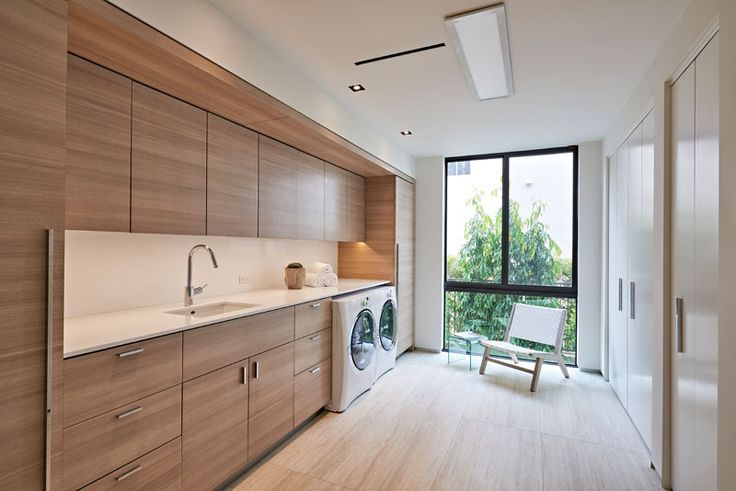 9 Inspirational Laundry Rooms You Need In Your Life // This laundry room has lots of natural light, a wall full of wooden cabinetry, and on the opposite wall, tall wardrobes create additional storage.