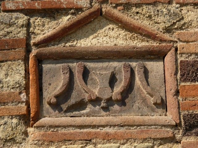 """VI.14.28 Pompeii. July 2010. Plaque on outside wall showing a """"fritillus"""" between four phallus."""