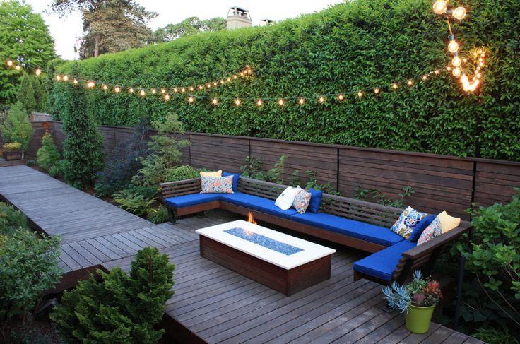 brise-vue terrasse en bois massif, haie verte, foyer extérieur, canapé en U et fleurs en pots