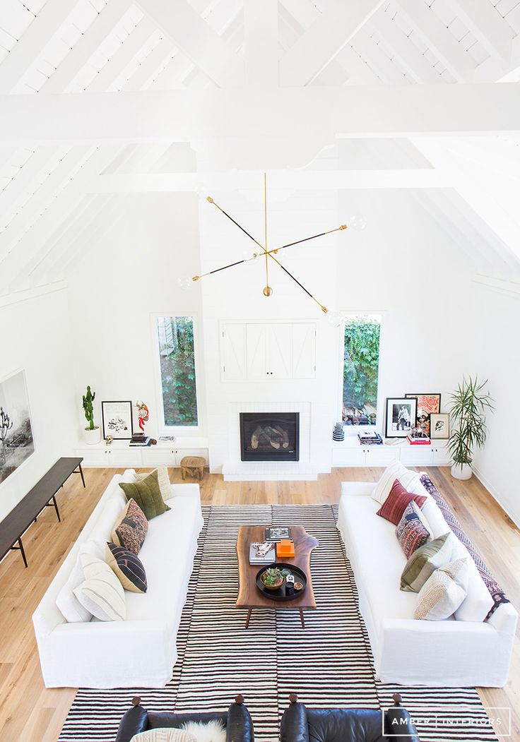 Open living room with white couches, brass chandelier, and geometric rug | Amber Interiors