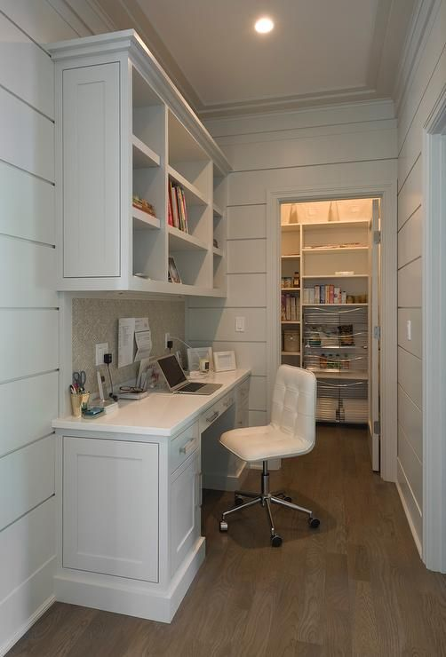A kitchen hallway leading to the pantry boasts open shelving suspended over a built in desk with a fabric pin board backsplash paired with a white tufted leather work chair.