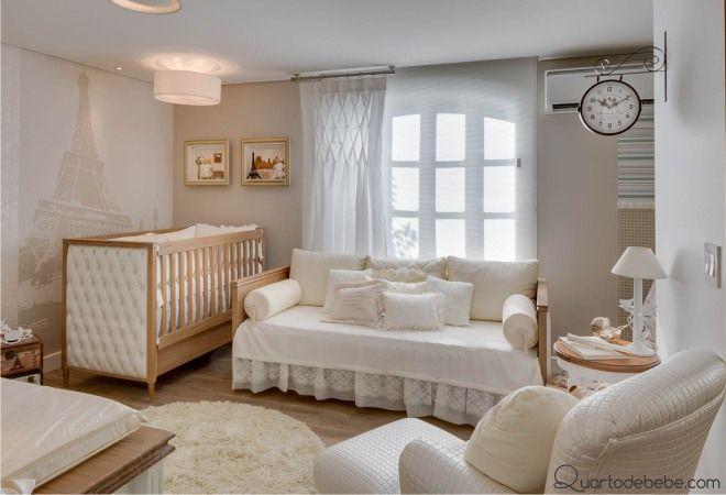 Quarto de bebê com berço cor madeira e enxoval Francês e papel de parede da Torre Eiffel, cama de babá e um relógio de teto antigo inspirado no metrô. Paredes pintadas nas cores areia e branco.