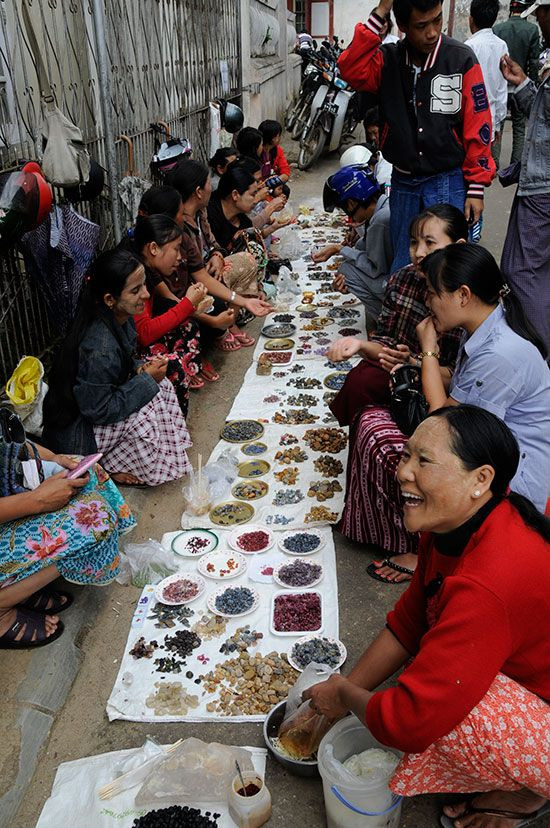 Women's gem market in downtown Mogok, Burma. Negotiating with a dealer, right, who smiles, indicating that she is winning. [It looks like they're selling rough sapphires and rubies] (Photo: Bill Larson)