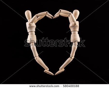 Two wooden figurines forming heart shape - love and relationship concept