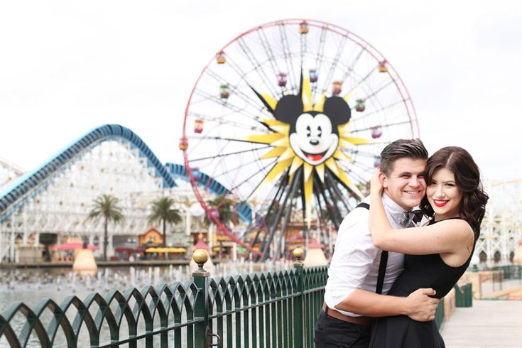 Couple in front of the ferris wheel at Disneyland theme park in California