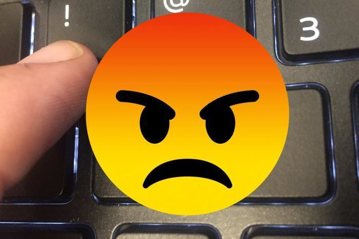 Angry emoji superimposed on keyboard