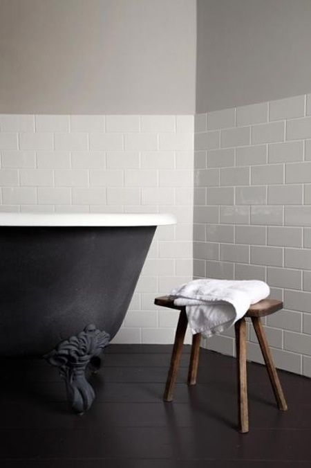 matt black bath, adorable old school stool, and half wall of subway tile. Lovely