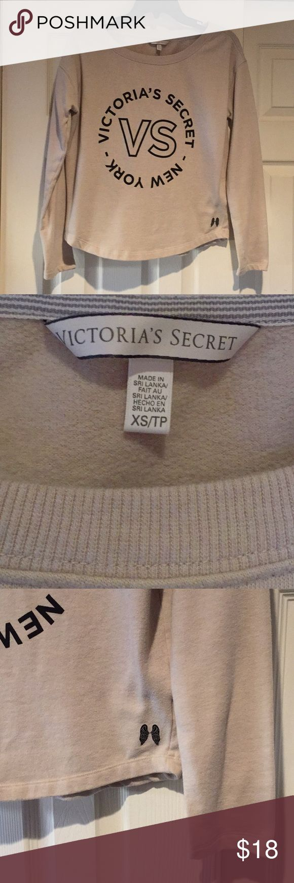VICTORIA'S SECRET BEIGE NEW YORK SWEATSHIRT  Beige super soft Victoria's Secret sweatshirt. Black lettering centered on the front of the sweatshirt. Size Extra Small.  Bottom of sweatshirt has a curved shaped. See pictures  Victoria's Secret Tops Sweatshirts & Hoodies
