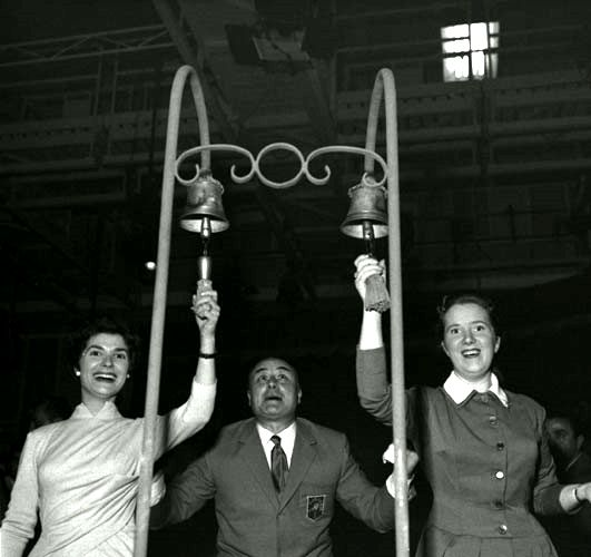 Mario Riva with two competitors of the musical quiz. The most popular of the quiz challenges was the guessing of a series of songs. For every song, the two competitors started from a rocking chair and, after a short run across the stage, she or he had to be the first to ring a ship bell to gain the chance to answer.