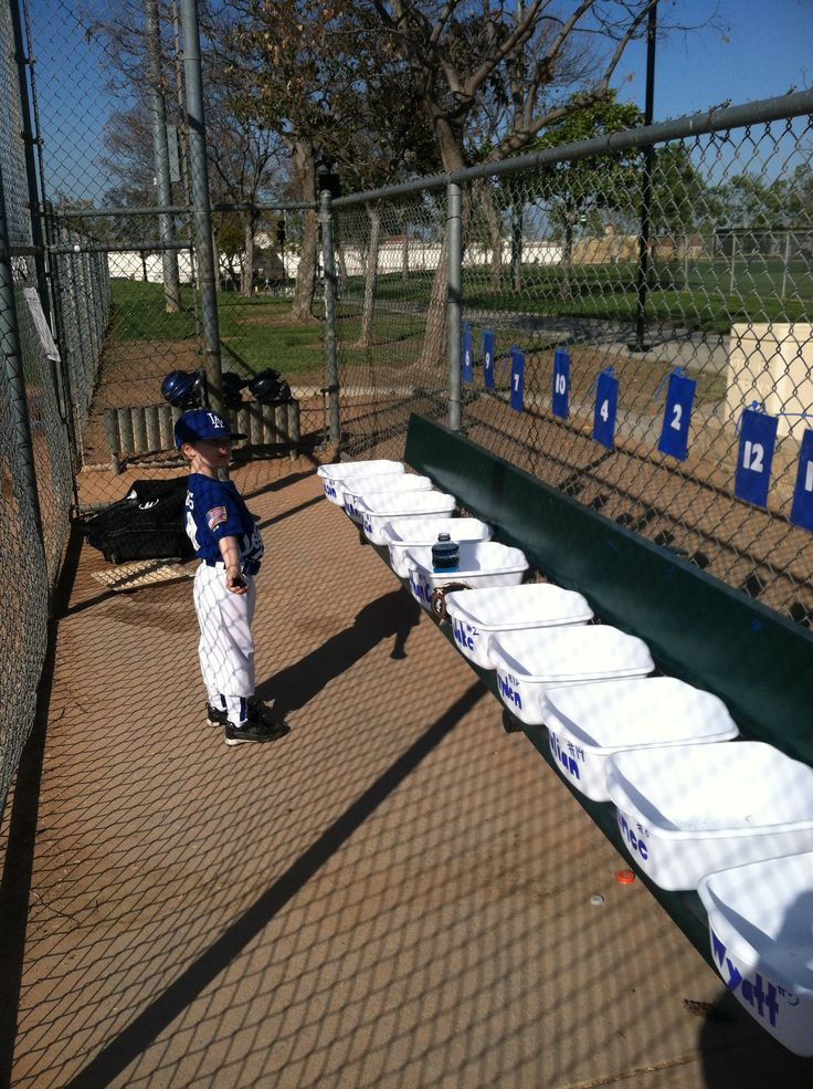 Organized TBall Dugout. Bins with players names on it for hats, gloves, water bottles etc. numbers on the fence to know where they sit in line up. Only took one unorganized game to come up with this system and it works great!