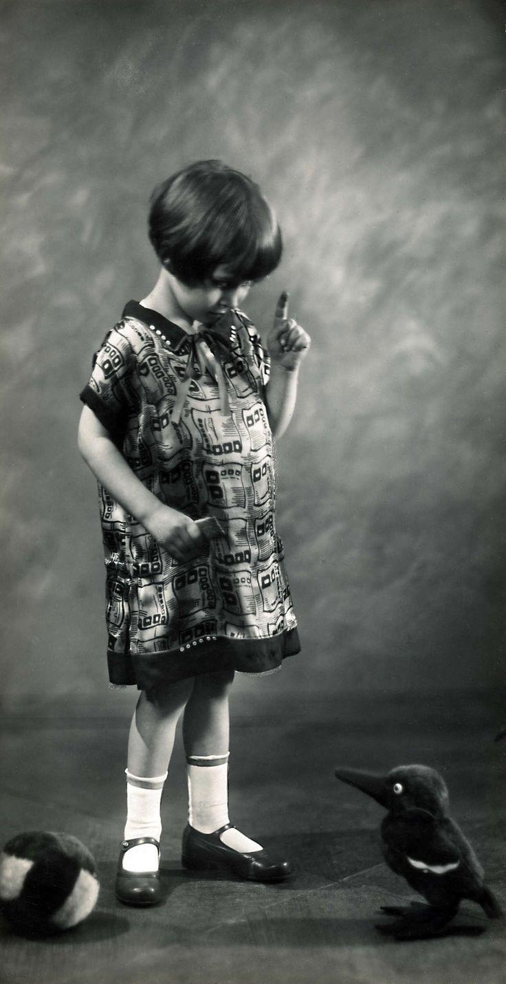 Mode. Kinderkleding. Een klein meisje in een jurkje van bedrukte stof en zijden biezen. Duitsland, 1926.