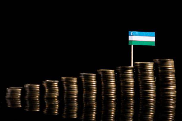 uzbekistan flag with lot of coins isolated on black background