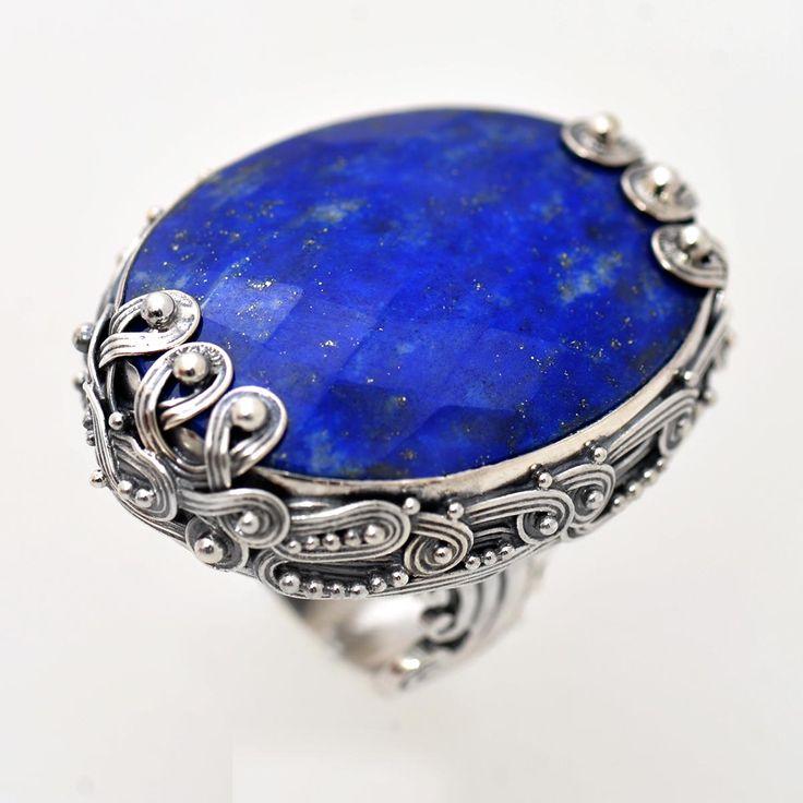 Inel din argint realizat manual, customizat la forma și dimensiunea pietrei de lapis lazuli, gemă naturală semiprețioasă tăiată oval, fațetată, bogat ornamentată pe ramă și verigă în tehnica granulației. Cod produs: VI5773 Greutate: 24.57 gr. Lungime: 3.50 cm Lățime: 2.50 cm Circumferință inel: 55 mm Piatră: LAPIS LAZULI